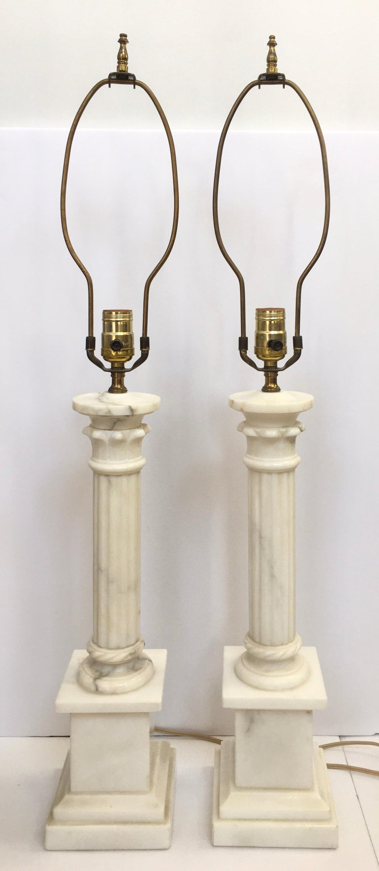 Pair of classic neoclassical style 'ionic column' solid marble pillar table lamps. These tall buffet lamps feature polished white marble with grey veining. Beautifully carved fluted columns are mounted on square plinth bases. Lamp shades not