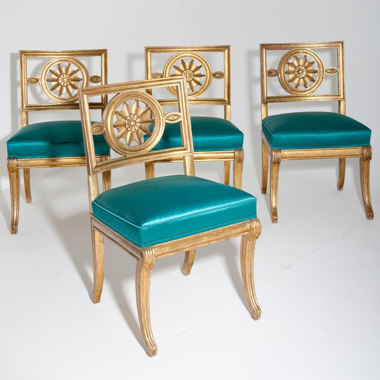 Four gilt chairs and one armchair with curved legs and backrests with a star shaped décor element. The chairs were reupholstered with a high-quality turquoise-blue fabric. The original chair was designed for Castle Wörlitz. 