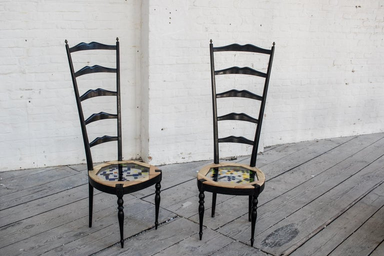 The tall mosaiced chairs are in their style similar to the chairs of the famous designer Mackintosh who inspired many artisans at the beginning of the 20th century as this couple of antique chairs shows. The original sitting has been replaced with a