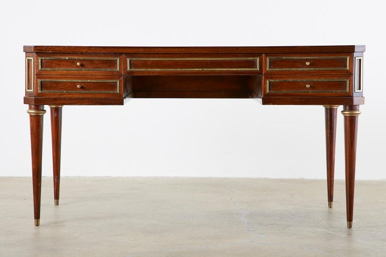 Distinctive mahogany writing table or desk featuring a case embellished with brass panel accents and fronted by three large storage drawers. The case is rectangular with angular clipped corners and supported by bronze mounted round tapered legs
