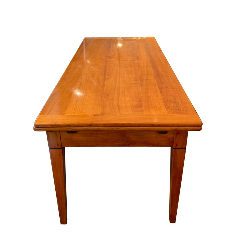 Large neoclasscial, rectangular Biedermeier or French Restoration extending / expandable Dining room table. Expandable up to 157 inches. Beautifully solid cherry wood, hand-polished with shellac. Two extension leaves a 100 cm with chestnut wood