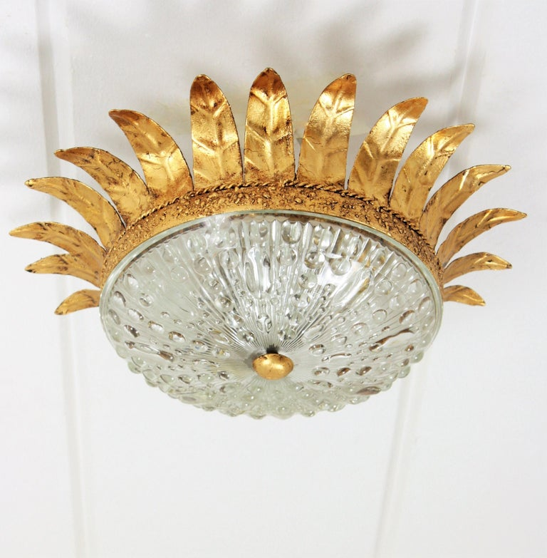 An sculptural hand-hammered iron and glass ceiling sunburst light fixture in neoclassical style with Brutalist accents. A hand-hammered gilt iron sunburst crown fixture with a pressed glass shade with a gilt iron ball finial. This lamp has an highly