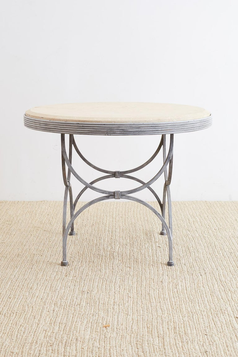 Extraordinary iron and stone patio garden table made in the neoclassical taste. Features a thick molded stone top with a beveled edge. The elegant base has a reeded edge and is supported by curved curule style legs conjoined on top and bottom.