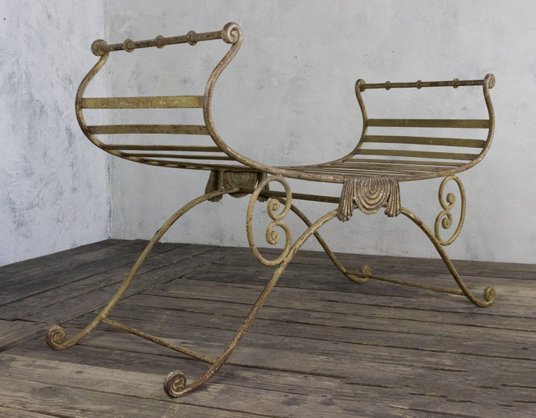 Neoclassic style wrought iron bench with distressed paint finish.