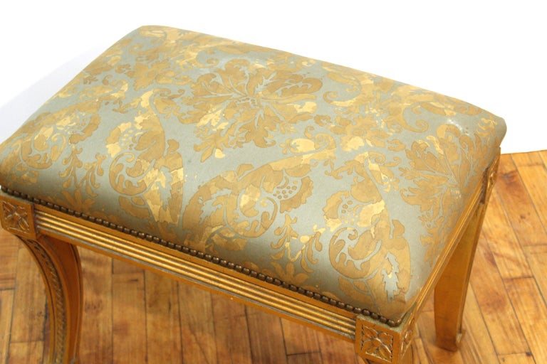 Neoclassical Revival style carved giltwood bench with swung legs and upholstery. In great vintage condition with age-appropriate wear and use.