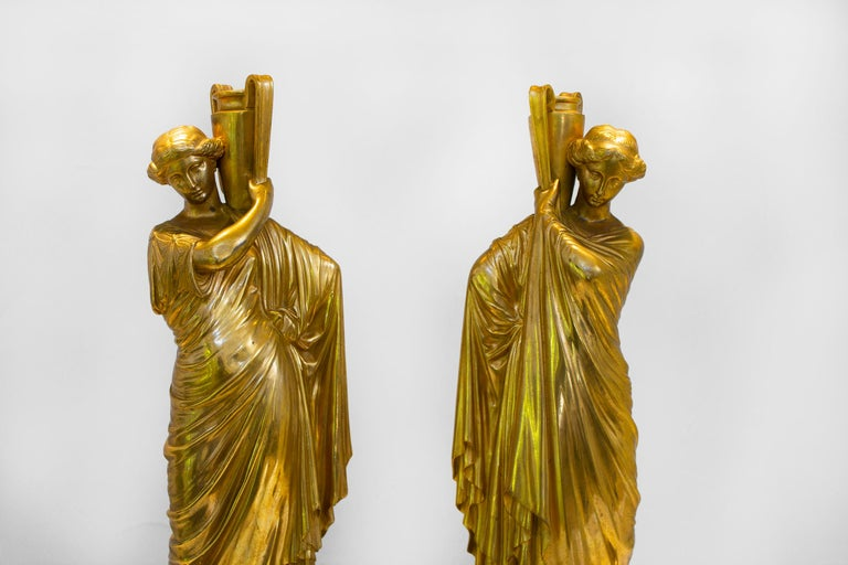 Gorgeous pair of antique golden cast bronze roman women on newly fabricated marble bases. They are hollow and the water jugs are open so they can be used to display an arrangement without water.