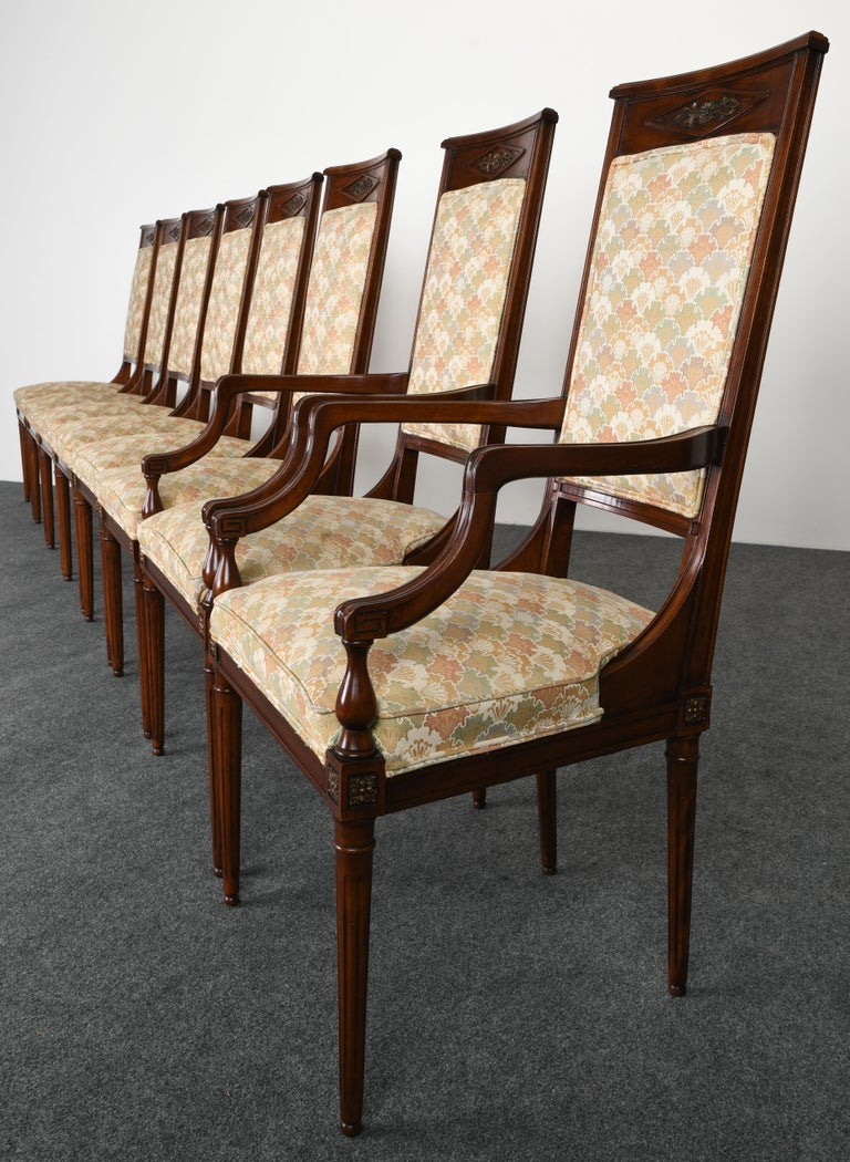 An elegant neoclassical style set of eight mahogany dining chairs in the style of Karges Furniture Company. Very good vintage condition with age appropriate wear. One ball foot has chip not noticeable, as shown in images. Hand carved crest flower