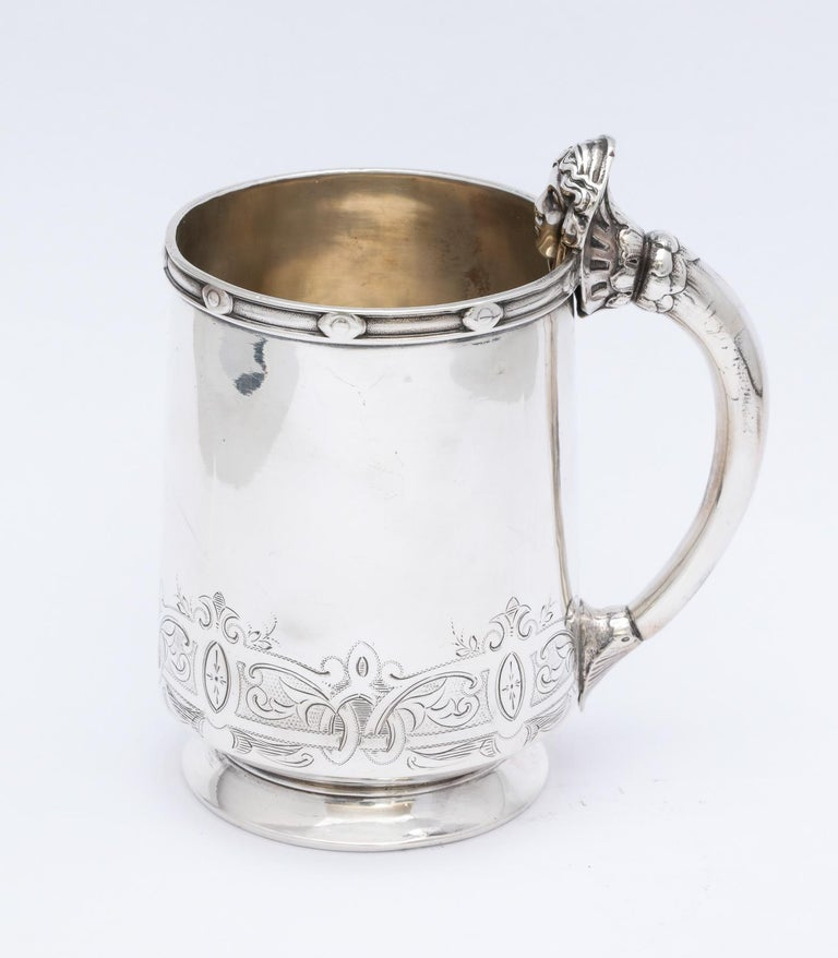 Neoclassical, sterling silver child's mug/cup, Gorham Mfg. Co, Providence, Rhode Island, circa 1860. Handle is decorated with a neoclassical woman's head. Interior is lightly gilded. Decorative border along top edge; etched work along bottom of cup.