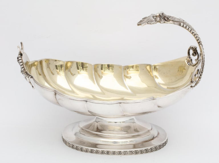 Neoclassical, sterling silver, parcel gilt, pedestal based sauce/gravy boat, New York, Ca. 1870, Wood and Hughes - makers. Shell - form scalloped interior is gilded; bead work motif on handle is continued on base. U-shaped opening on top of