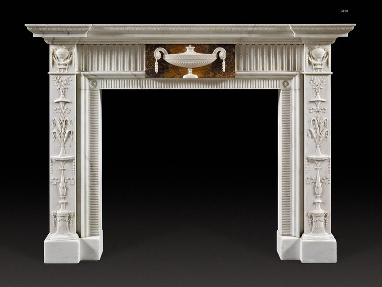 The breakfront, moulded shelf above the frieze which is centred with a tablet carved with tazza shaped, lidded urn in statuary on sienna marble. This is flanked by bands of flutes; the blockings above the pilaster, arabesque decorated jambs with