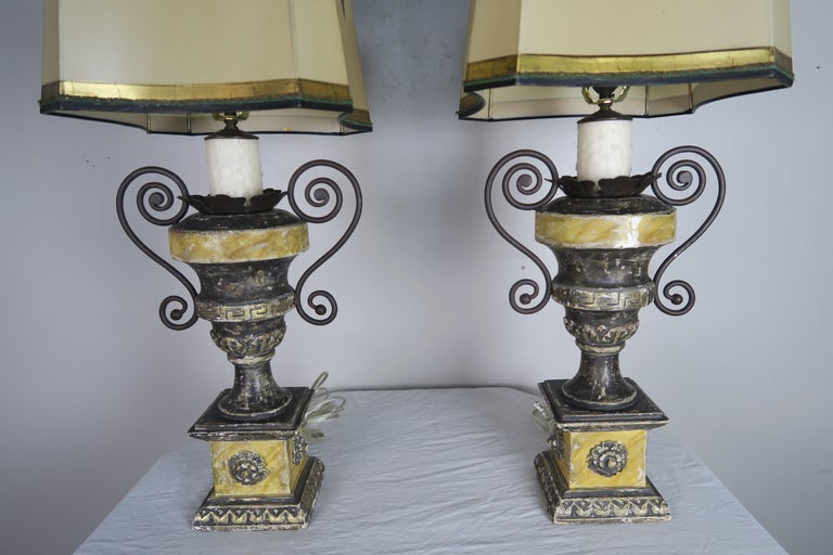 Pair of neoclassical style carved painted urns with silver gilt highlights and Greek Key design. The lamps are newly rewired with drip wax candle covers. The lamps are crowned with hand painted rectangular shaped shades with scooped corners.
