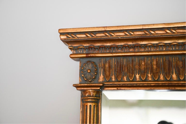A gold painted wall or over the mantel (fireplace) mirror. Capital over column-form sides and base making this mirror easy to sit upon any mantel, fireplace or tabletop. Wall, console or overmantle mirror.
