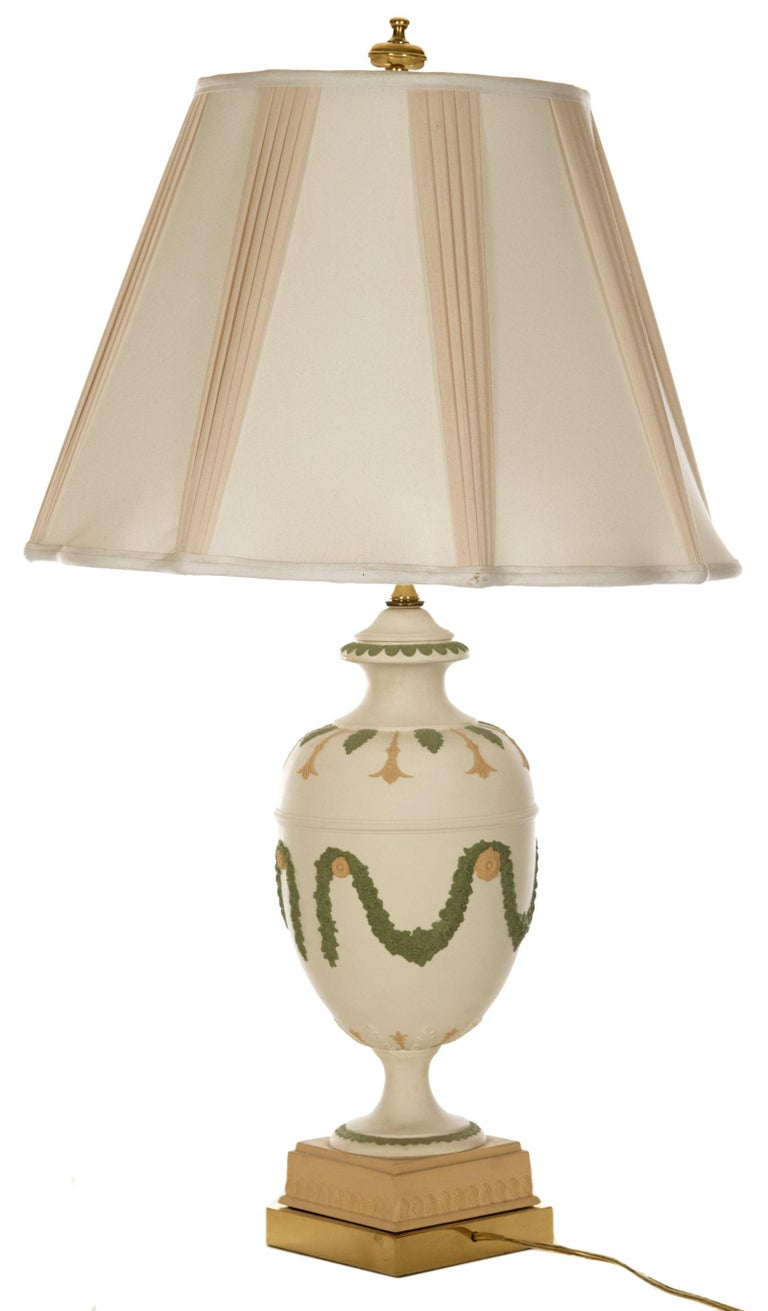 A neoclassical style ceramic table lamp of baluster form decorated with soft green and cream acanthus leaf motifs around the neck and shoulders of the form, the body with medallions supporting foliate garlands, raised on a square, cream plinth base,