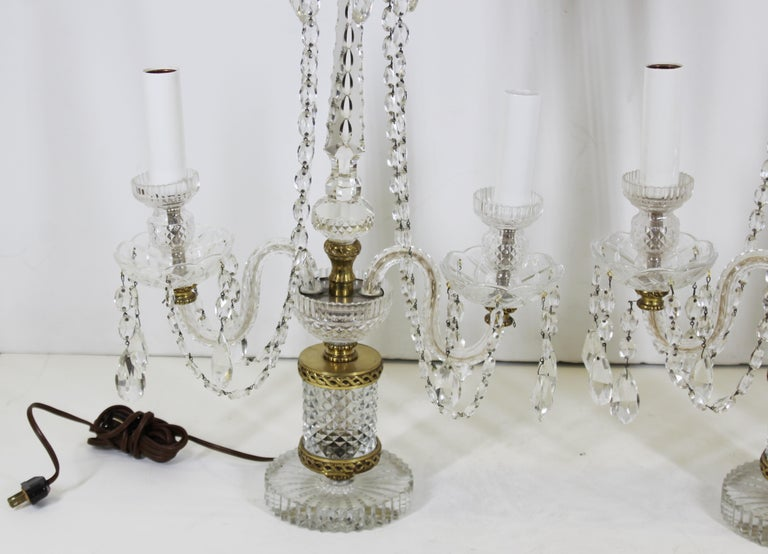 Neoclassical style pair of crystal lamps with droplets and gilt metal elements. The pair was made in Czechoslovakia likely around the mid-20th century. In great vintage condition with age-appropriate wear and use.