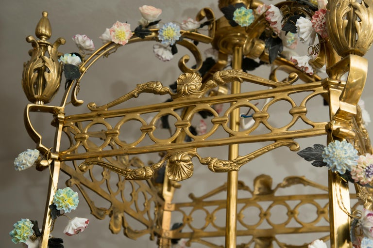 This is a very romantic neoclassical style gilt bronze lantern-form chandelier-encrusted overall with a plethora of multicolored porcelain flower heads, early 20th century.