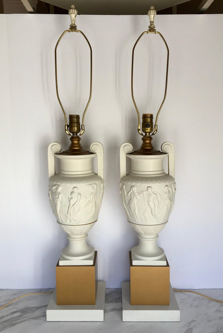 Pair of neoclassical style ceramic and wood urn table lamps mounted on square plinth gold wood bases. Plaster-like matte cream handled urns feature sculptural relief figures. Lamp shades not included.   Measures: Height to harp: 35.5