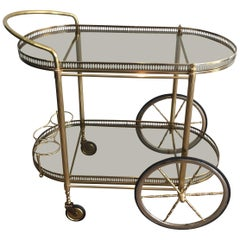 Neoclassical Style Oval Brass and Gilt Bar Cart with Greenish Smoked Glass