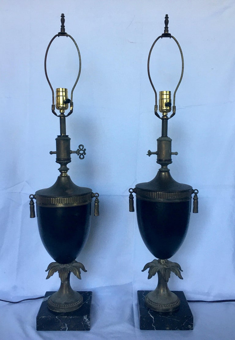 Pair of neoclassical style urn form table lamps mounted on black marble plinth bases. Matte black metal urns feature decorative brass tassels and fluted decorations. Lamp shades not included.   Measures: Height to finial: 33 inches.  Height to