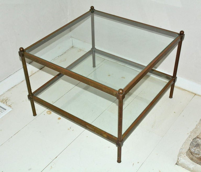 Maison Jansen style two-tier square brass contemporary coffee table has inset glass surfaces and is square. Original and beautifully aged brass patina but can be polished if a more sleek look is desired or suitable.