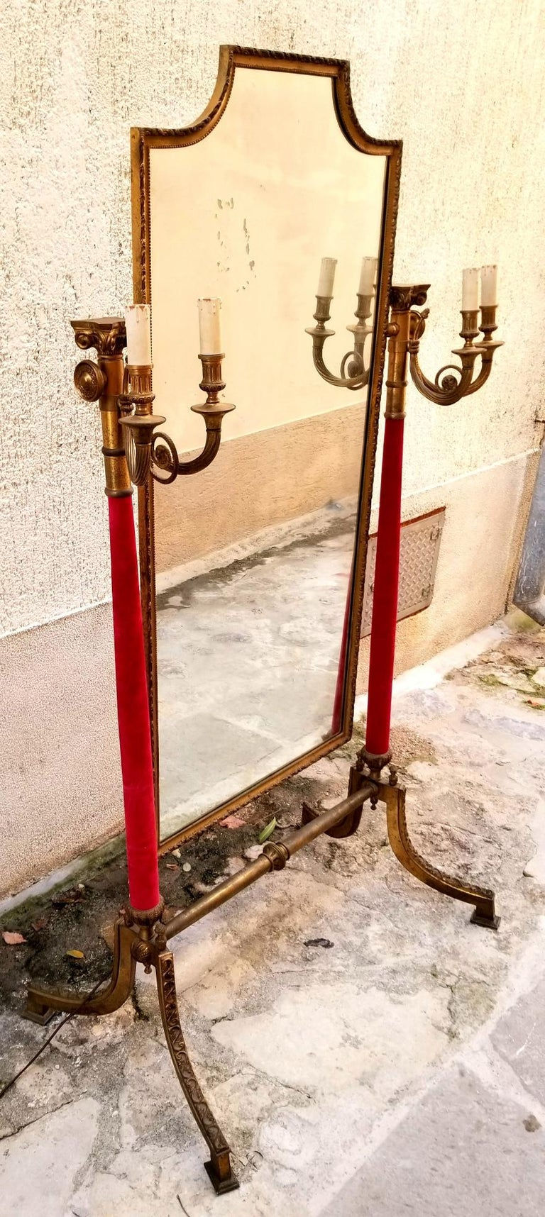 Italian brass mirror from Venice boutique at San Marco square. Mirror is a full size length and adjustable like a chevalier mirror. The mirror itself is 53 height and 25 width. The candle cover is hand carved wood and the rest is brass. The red