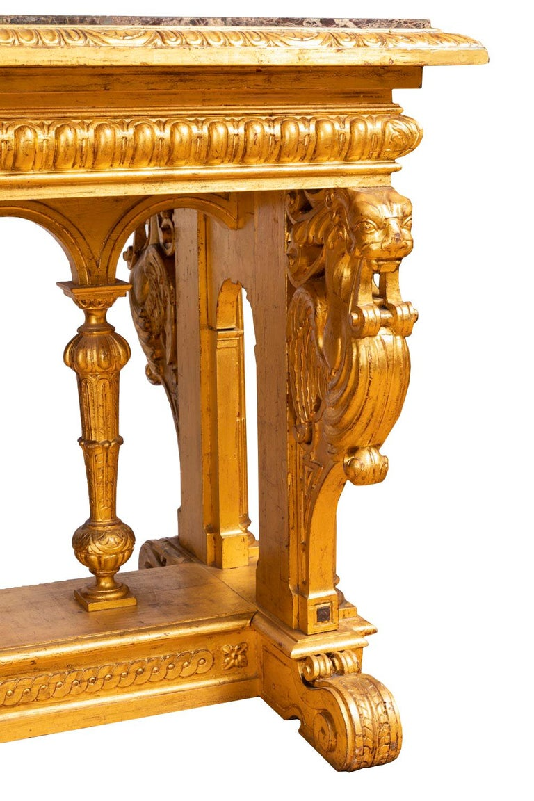 "Renaissance style table in giltwood standing on four short small feet in shape of flattened foliage scrolls. Stand in the style of Roman cartibulum, in French called ""fan"" table because of the shape of the stand. A crossing adorned with interlaces"