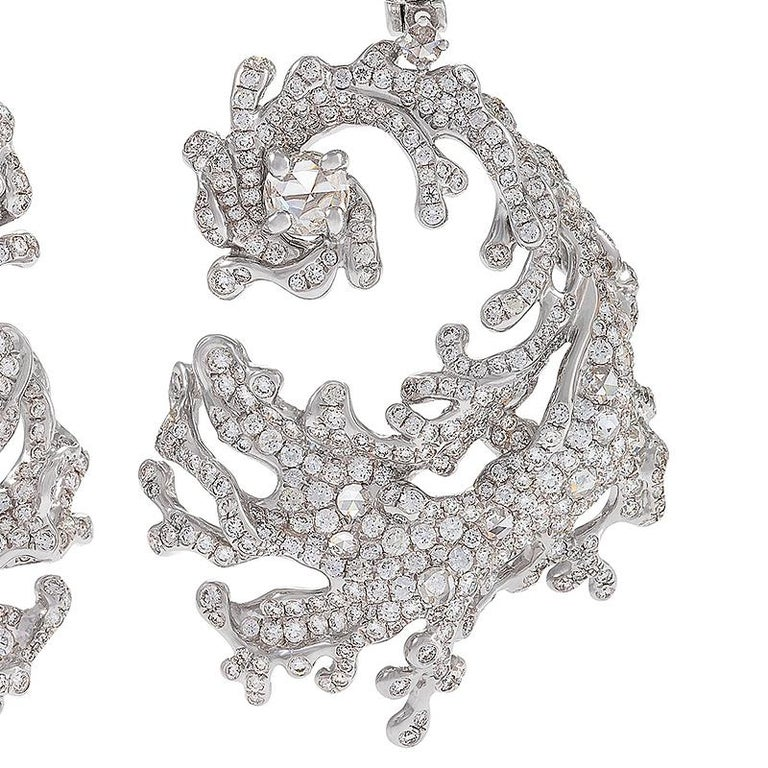 A pair of modern Nerissa earrings by Neha Dani. These earrings are dramatic concentric swirls which capture the power and grace of large cresting waves. They belong to an aesthetic grouping of Neha Dani's work that mimics the appearance of a