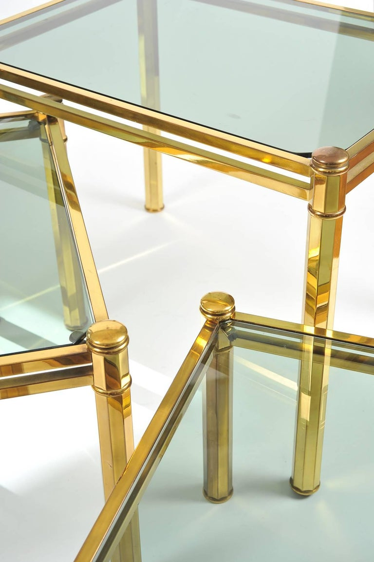 Nest of three Italian brass side tables with octagonal-planed legs. Each table inset with smoked glass top. Middle table measures 13.5in high x 19in wide x 16in deep. Small table measures 10.75in high x 16.25in wide x 16.25in deep. Measurements for