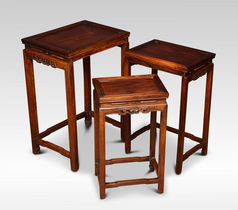 Nest of three Chinese rosewood tables, each with a recessed panel to the rectangular top and a carved frieze on four slender supports with conforming stretchers.