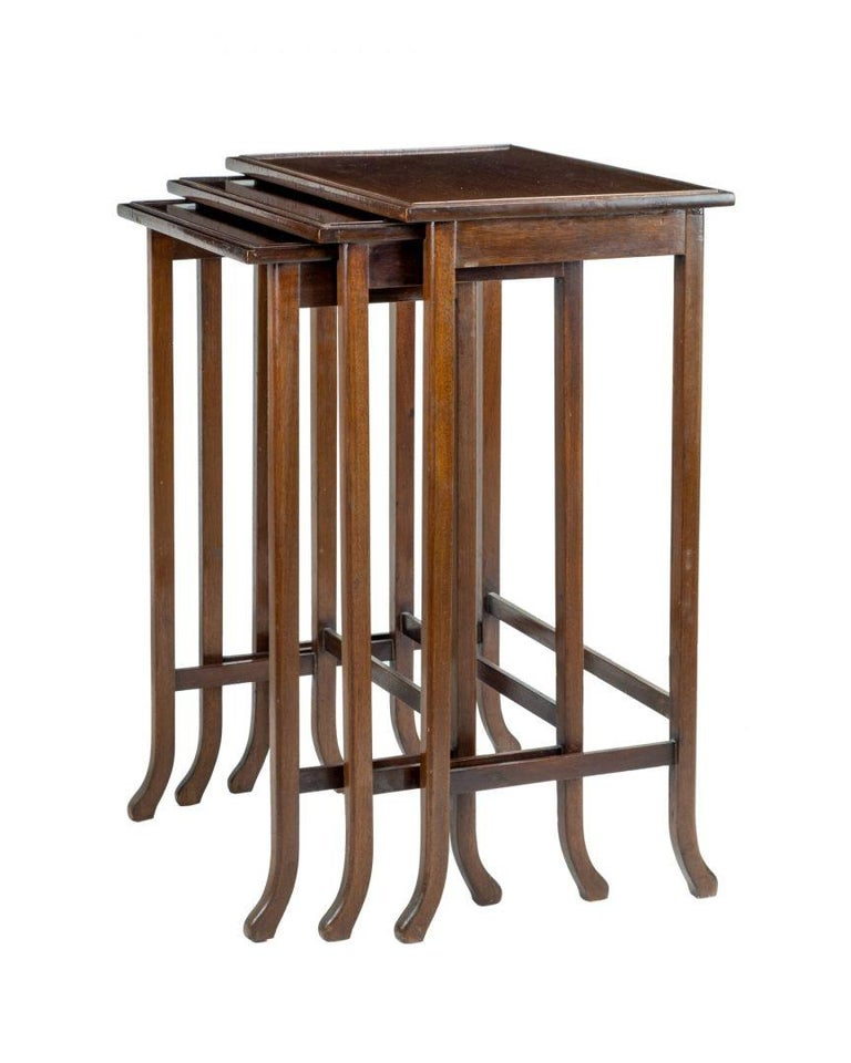 A nest of three mahogany tables, by Waring and Gillow, each impressed G.L and M to the underside