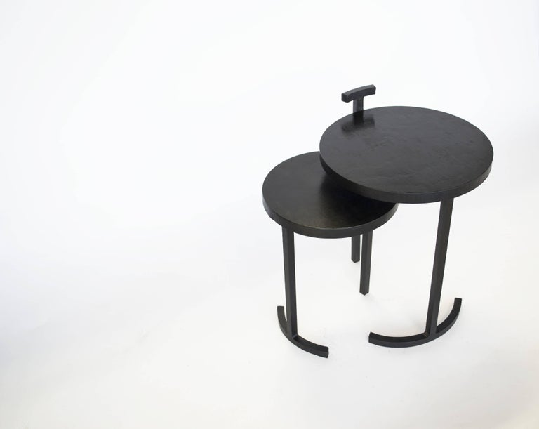Table pair no. 1 J.M. Szymanski d. 2017  A striking designs composed of two separate side tables. Each table has only two legs! This nesting side table set is made from cast blackened and waxed steel. A uniquely designed frame allows a 1 inch