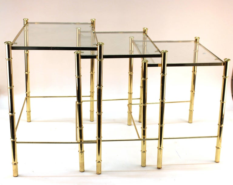 Nesting table and magazine holder set in gilt metal from France. Crafted with faux bamboo motif. Set includes three tables with gilt frames and glass tops. The magazine holder features a faux bamboo handle, criss cross pattern on sides and faux