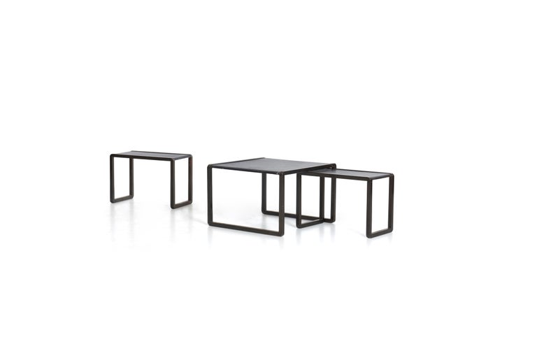 Marco Fantoni for Tecno, these unique nesting tables were designed for Borsani Commission. Bronze painted metal with leather tops. Measures: Height of largest table 16