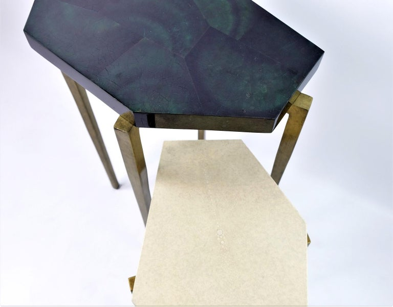 These futurist nesting tables are made of natural shagreen (Our ref ANTIC) and polished green penshell marquetry.  They have a polygonal shape top and the feet have an antique brass patina.  The tables are small and very versatile. These can be