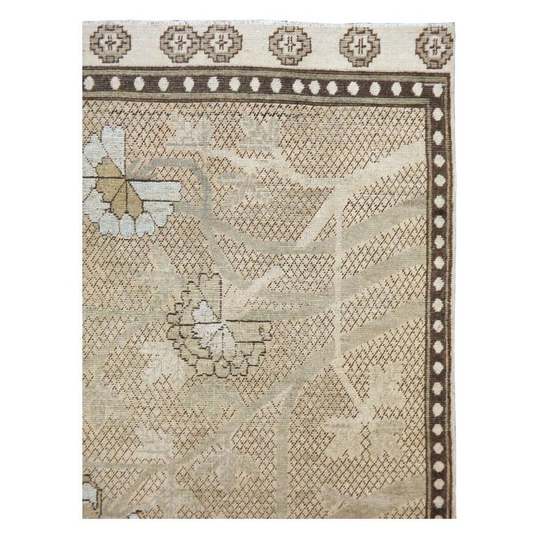An antique East Turkestan Khotan accent rug in gallery size format handmade during the early 20th century. The beige field consists of a calming brown diamond lattice pattern with a peony tree drawn on top. The peony tree is made up of a palette in