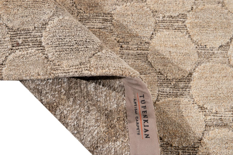 Beautiful modern Tibetan Tufenkian hand knotted wool rug with the tan field. This rug has a gorgeous all-over Textured geometric Circle design.  This rug measures: 9' x 12'.