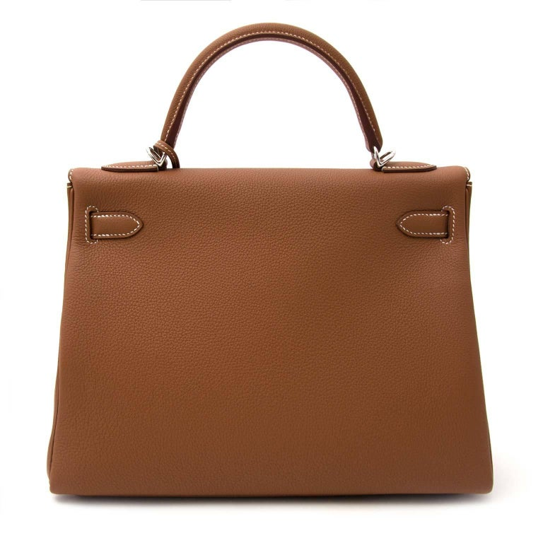 Hermès Kelly 32 Togo Gold PHW  This Hermès Kelly comes in a timeless gold color and is made out of Togo leather which has a smooth and grainy texture. The palladium hardware finishes of the look contrast beautifully with the warm gold leather.  It's