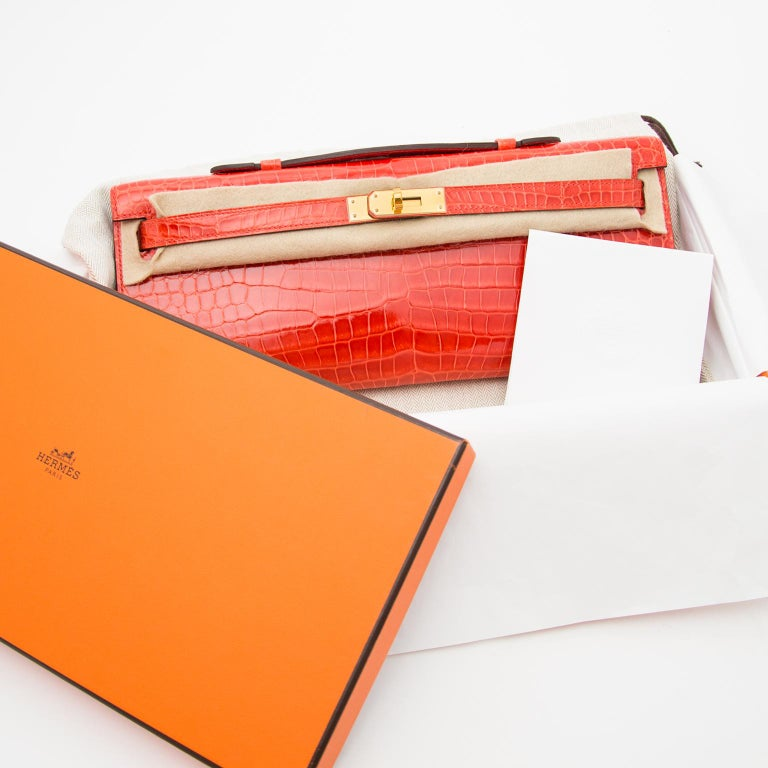 VERY RARE- HOW AMAZING this impossible find.  Pochette Kelly Cut Crocodile porosus lisse in the bright orange poppy.  We love the combination with the gold hardware.  The pochete is brand new and never used. Comes with full set, including original
