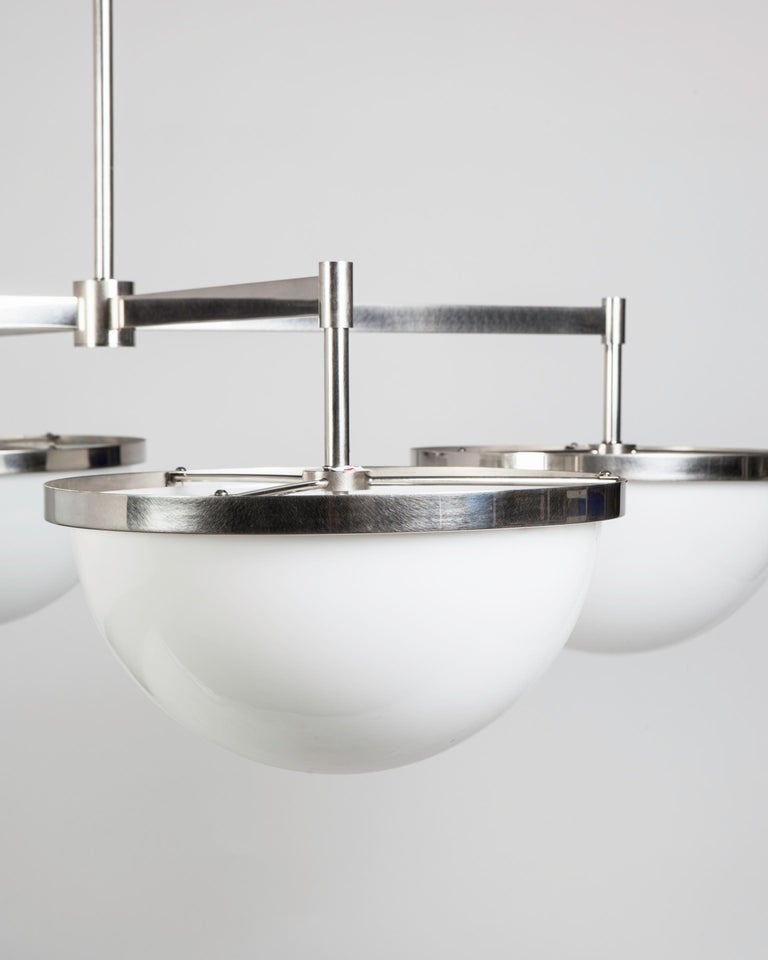 WHL2227.14 Designed by Alan Wanzenberg for Remains Lighting, the four arm Nevins 14 chandelier is the most simple and elemental of fixtures; with a set of four pure milk glass domes suspended in ribbons of unadorned metal, with rectangular