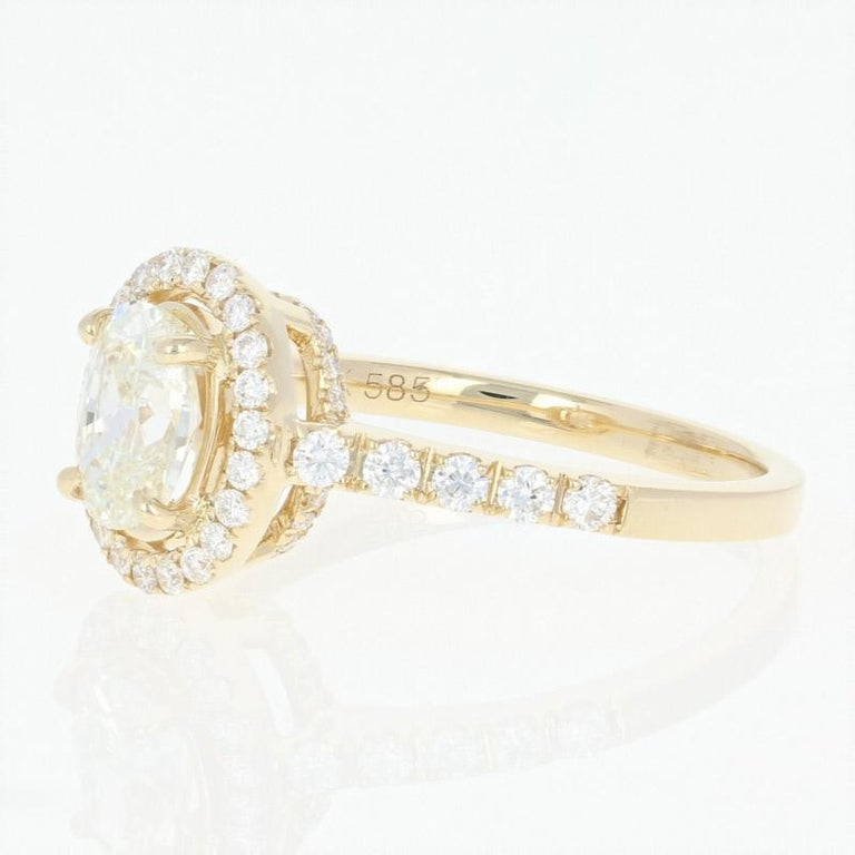 Begin the next chapter of your cherished love story with this breathtaking engagement ring! Featured in a dazzling 14k yellow gold halo-style mount, this NEW ring showcases a resplendent GIA-graded diamond solitaire that is beautifully accompanied