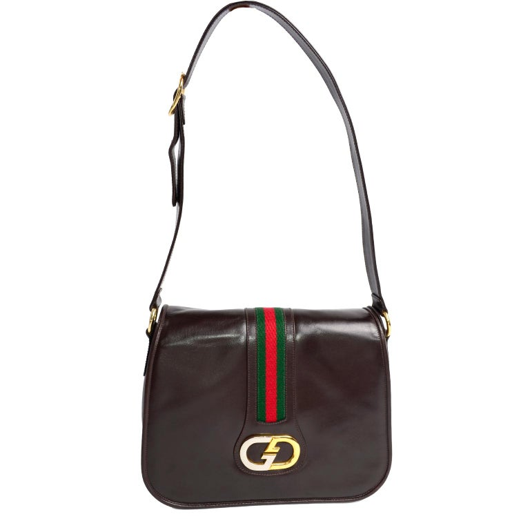 This is a classic vintage Gucci brown leather bag purchased at Joseph Magnin in 1979. This wonderful handbag still has its original tags attached and is accented with the iconic Gucci monogram buckle in silver and gold, and  Italian red and green