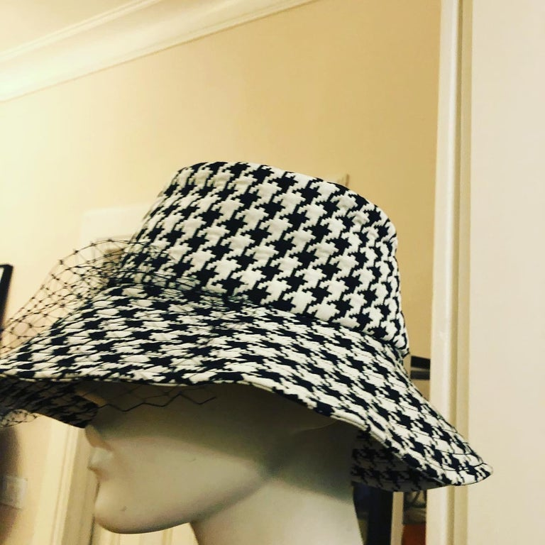 Elegant black and white houndstooth large brim well crafted hat., which pays hommage to the House of Dior. The brim is embellished with a black veil. It is foldable for travel. The hat comes with a dust bag, box and receipt which was $1437.19 Can