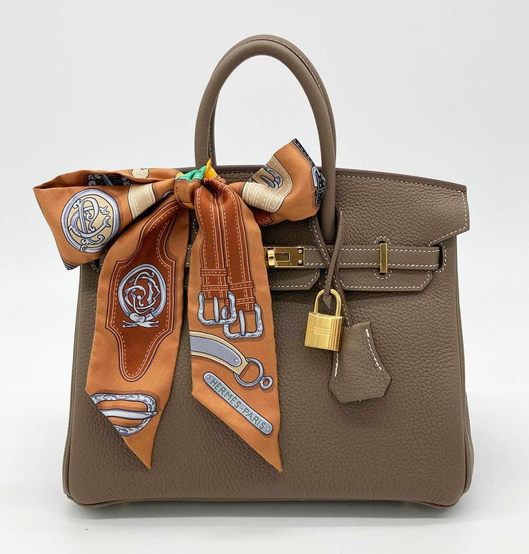 NWOT Hermes Etoupe Togo Birkin 25 GHW in mint unused condition. Etoupe togo leather exterior trimmed with gold hardware which still retains protective plastic covering. Signature birkin twist top flap closure opens to a matching kidskin lined