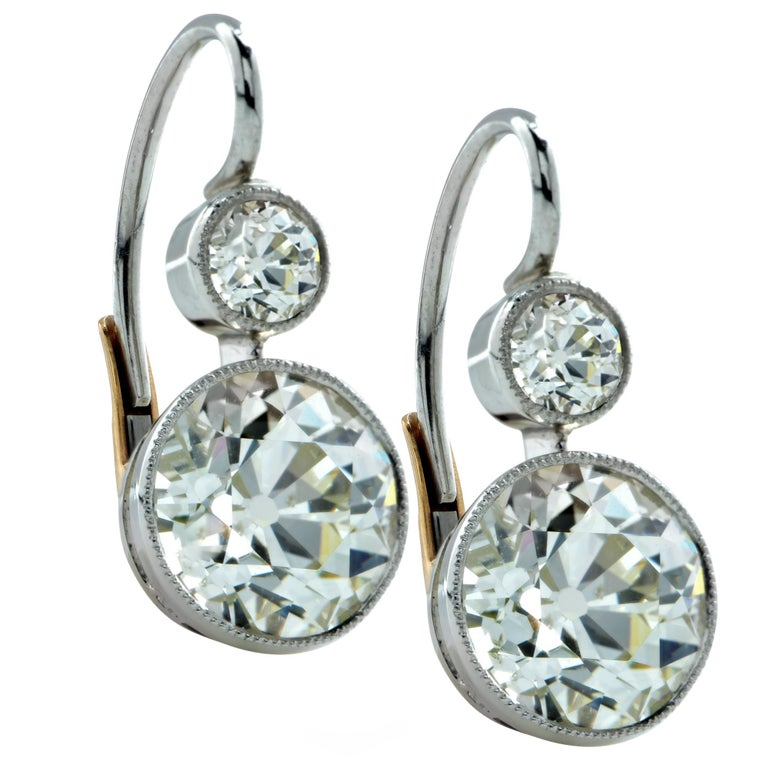Custom made Art Deco style dangle earrings crafted in platinum featuring 2 Old European cut diamonds weighing 6.17cts total, L-M color VS2-SI1 clarity accented by 2 Old European cut diamonds weighing .50cts total. L color SI clarity framed in