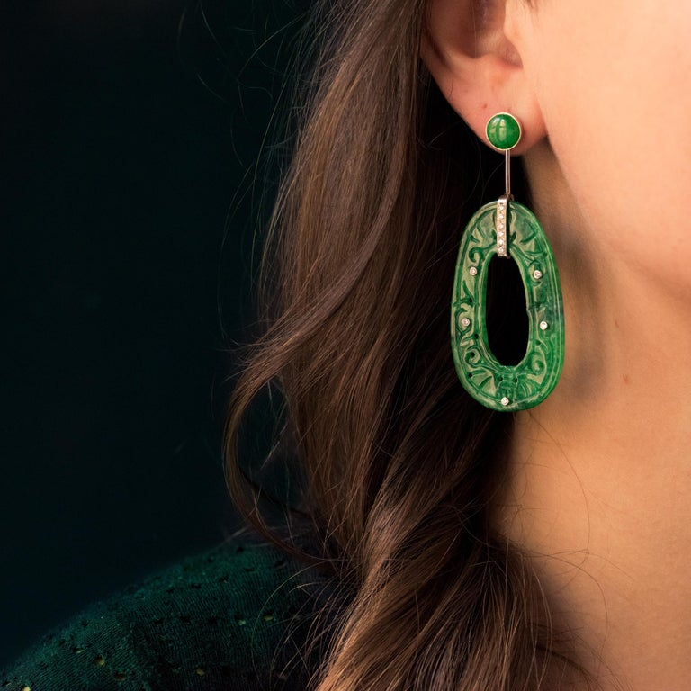 For pierced ears. Earrings in 18 carats white gold. These long art deco earrings are made of a green jade cabochon earring in pearly set with a removable gold stem, wich retains an oval shape jade engraved. The latter is openworked in the center,