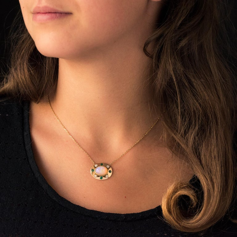 Baume Creation - Unique piece. Pendant in 18 karats yellow gold, eagle's head hallmark. Oval-shaped, this splendid and original necklace is adorned with an opal cabochon surrounded by alternating emeralds and brilliant-cut diamonds. The chain is a