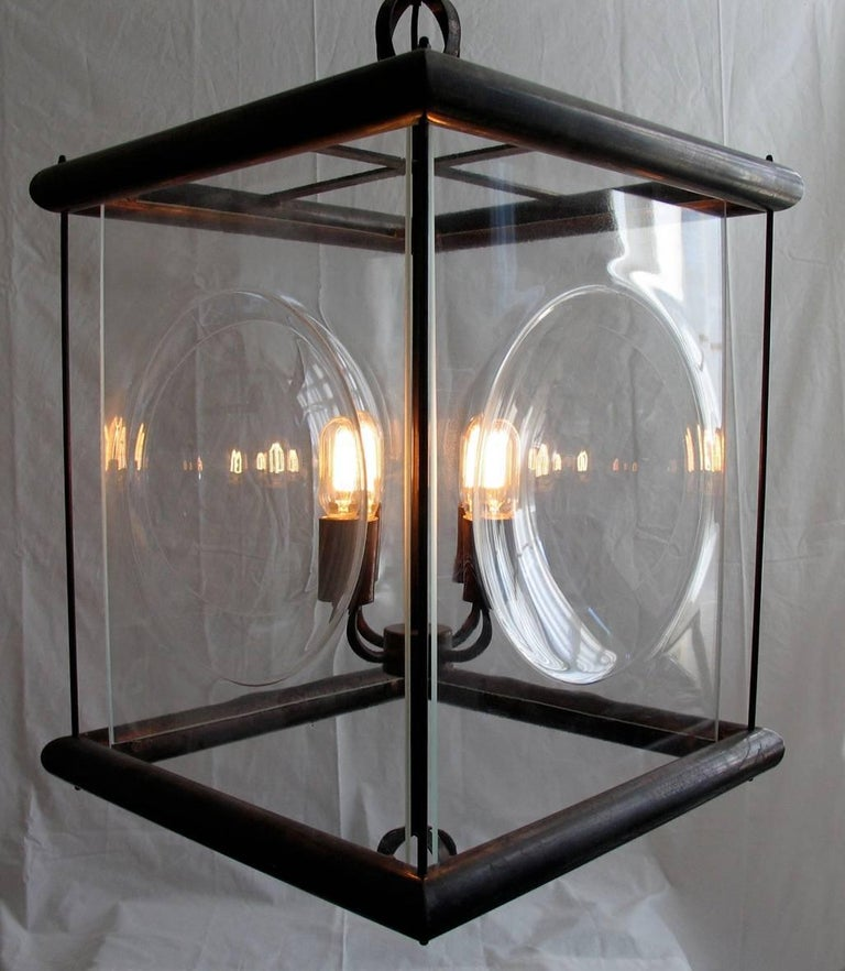 A timeless pendant lantern of brass tubing with a Rustic Bronze finish and slumped glass semi-sphere panels. Two spherical finials finish the design. 