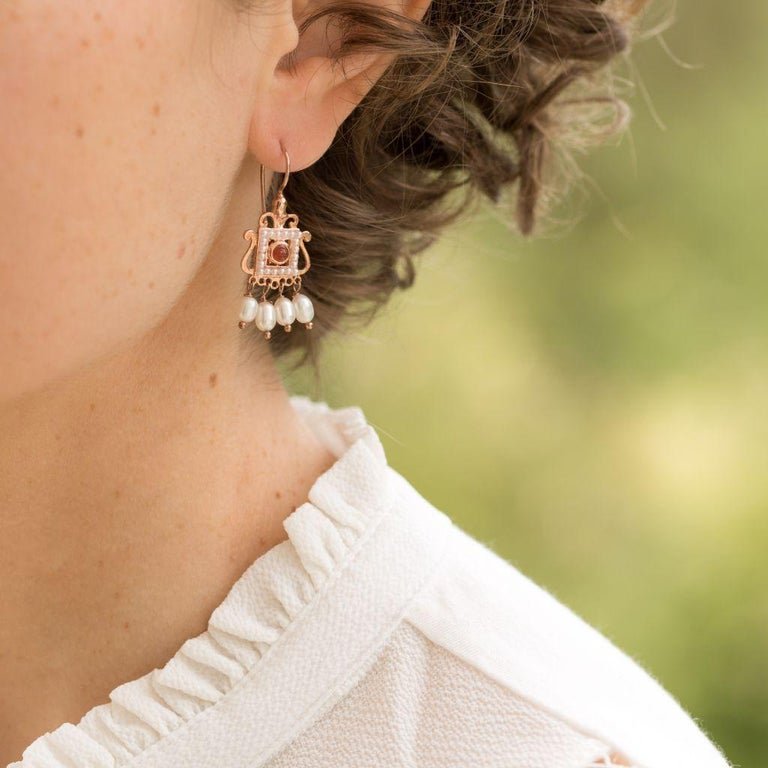 For pierced ears. Pair of earrings in vermeil, silver and rose gold.  Square in shape, they are each set in the center of a cabochon carnelian stone surrounded by white glass pearls. At the base in tassel, are hanging 4 baroque cultured pearls. The