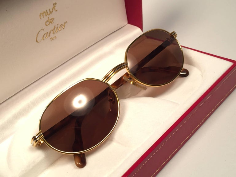 New Cartier oval Lueur sunglasses with spotless brown ( UV protection ) lenses. All hallmarks. Cartier signs on the ear paddles.  Both arms sport the knot from Cartier on the temple. These are like a pair of jewels on your nose.  Beautiful design