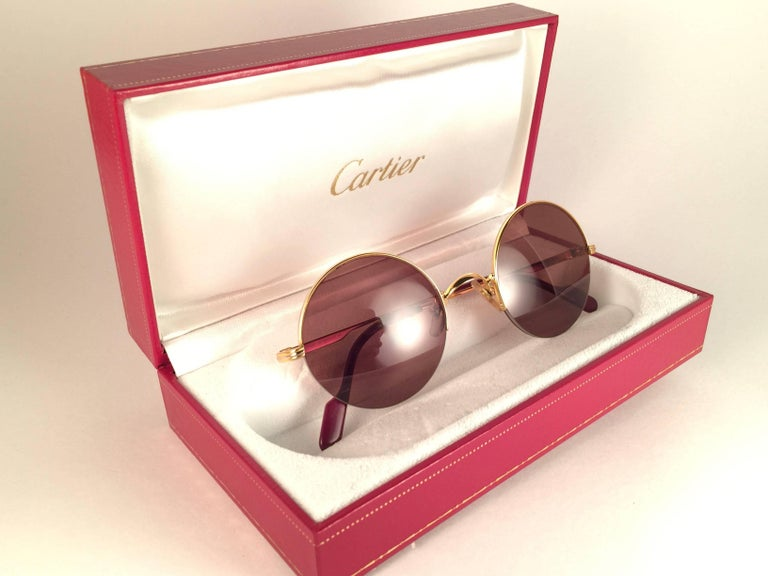New 1990 Cartier Mayfair half frame sunglasses with brown (uv protection) lenses.  Frame is with the front and sides in gold. All hallmarks. Cartier gold signs on the ear paddles.  These are like a pair of jewels on your nose. Beautiful design and