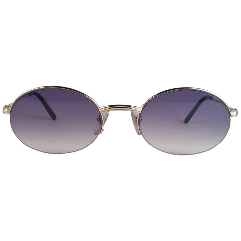 New Cartier oval Manhattan sunglasses with blue gradient lenses(uv protection).  All hallmarks. Silver Cartier signs on the ear paddles.  Both arms sport the knot from Cartier on the temple. These are like a pair of jewels on your nose.  Beautiful